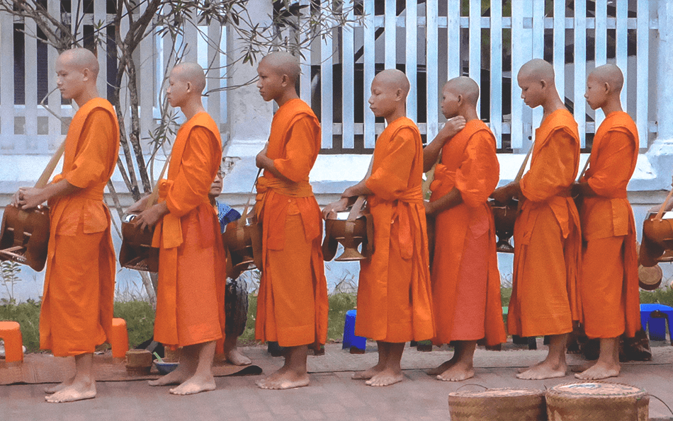 Morning alms ceremony where monks line up to receive their daily ration of food from locals
