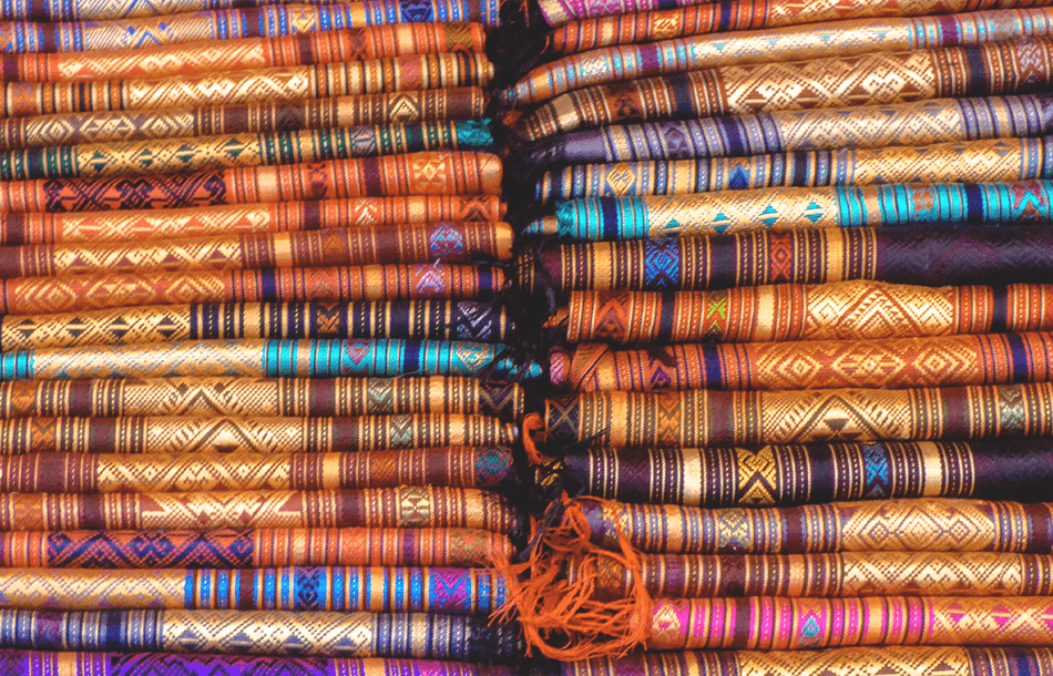 Fabrics in a rainbow of colours are being sold at the night market in Luang Prabang