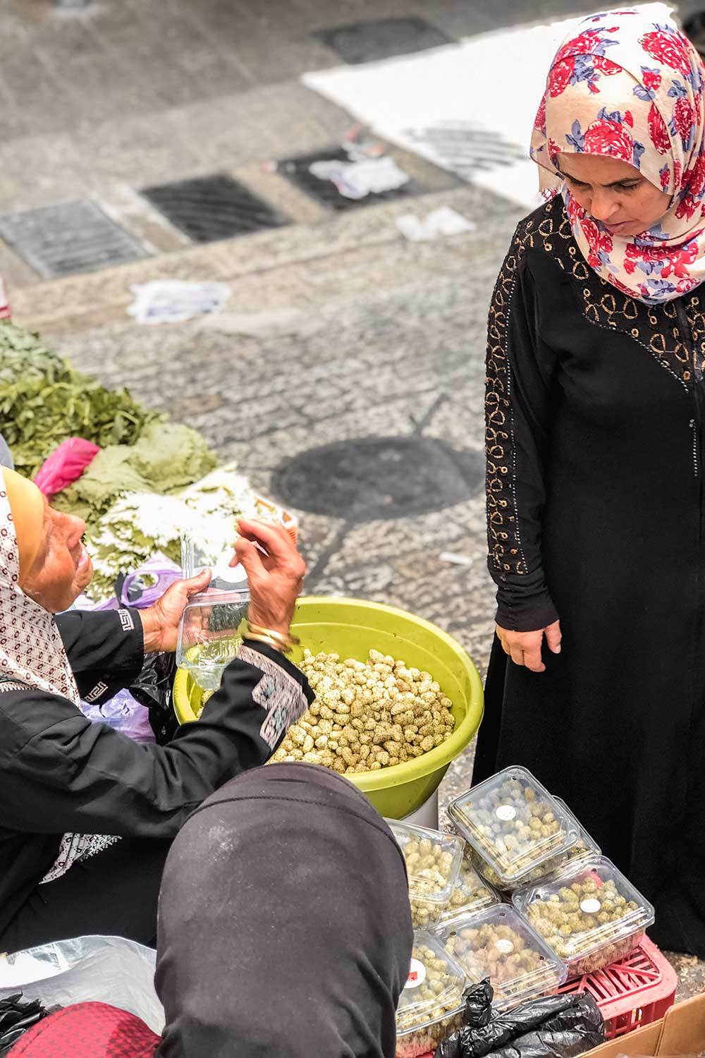 Women selling fruit and nuts at the entrance of the Arab Market
